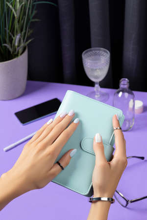 Womans hands holding notepad over violet table. Female summer accessories