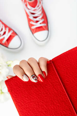 Beautiful young womans hand with red manicure on gray background