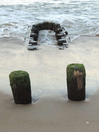 Pilings seem to take a bite out of the  ocean.