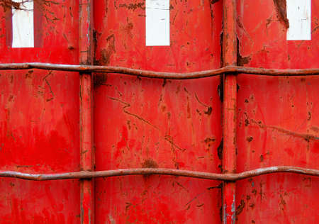 Detail of the side of a damaged, old, red container.