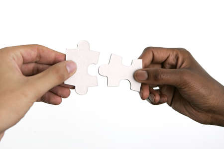 Hands trying to fit two puzzle pieces together, on white background