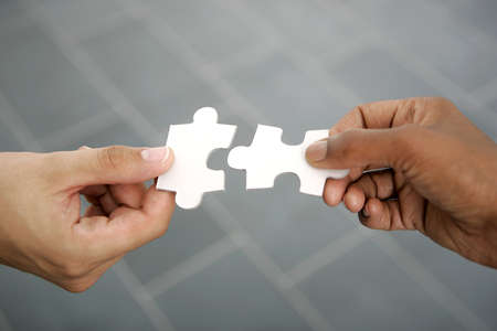 hands trying to fit two puzzle pieces together  Stock Photo