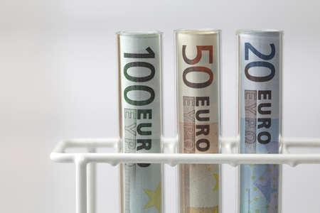 Euro banknotes in Test tubes on white background, healthcare costs concept 스톡 사진