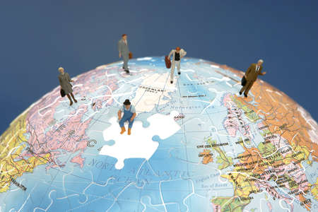 Business figurines standing on a globe  Imagens