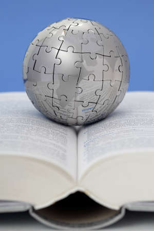 Metal puzzle globe on open book  photo