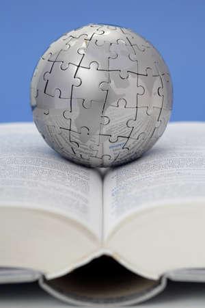 bibliotecas: Mundo de metal rompecabezas en el libro abierto  Foto de archivo