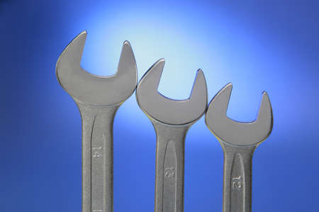 Tree steel wrenches of different size on blue background  photo