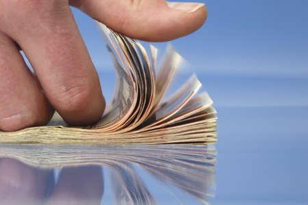contando dinero: Mano contando dinero, detalle sobre fondo azul con reflexiones Foto de archivo
