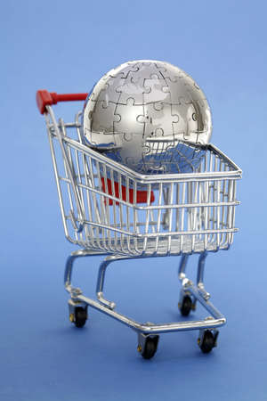 international internet: Metal puzzle globe with shopping cart on blue background