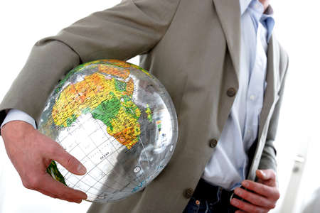 Businessman in motion holding a globe  Banque d'images