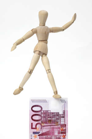 jointed: Jointed doll balancing on a 500-Euro-Banknote, on white background Stock Photo