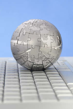 Metal puzzle globe on computer keyboard, on blue background  스톡 사진