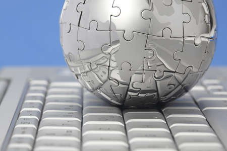Metal puzzle globe on computer keyboard, on blue background  photo