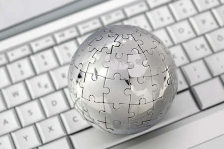 Metal puzzle globe on computer keyboard  Stock Photo