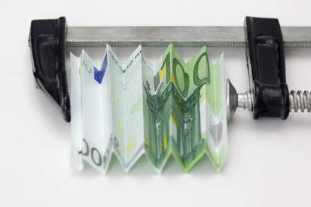 squeezing: One hundred euro bill squeezed in a clamp on white background