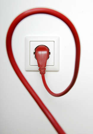 Red power cable plugged in electric outlet