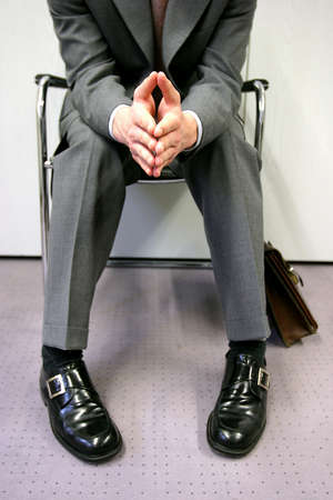 Person sitting impatiently, waiting for a job interview