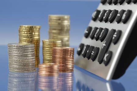 desktop calculator with coin stacks  Stock Photo