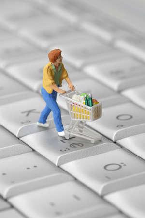 web commerce: Shopper in miniatura con carrello sulla tastiera di un computer. Concetto di shopping online.