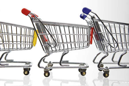 Mini Shopping carts in a row on white background photo