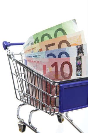 Mini shopping cart with euro banknotes on white background photo