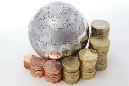 world economy: Metal puzzle globe with euro coins on white background