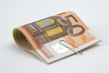 Fifty Euro bills with paperclip on white background