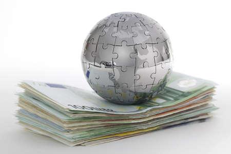 capitalismo: Mundo de metal rompecabezas con dinero sobre fondo blanco Foto de archivo