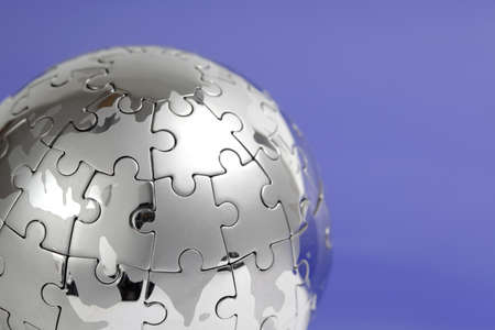 Metal puzzle globe isolated on white background, close-up on blue background Stock Photo - 9370075