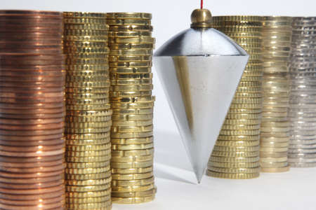 Plumb bob with coin stacks on white background Stock Photo - 9375180
