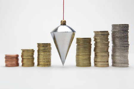 plumb: Plumb bob with coin stacks on white background