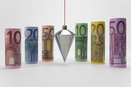 Rolled up Euro bills with plumb bob on white background photo