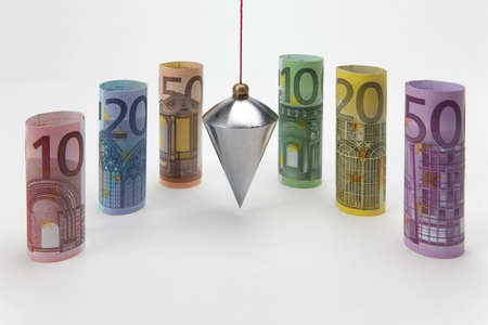 plumb: Rolled up Euro bills with plumb bob on white background