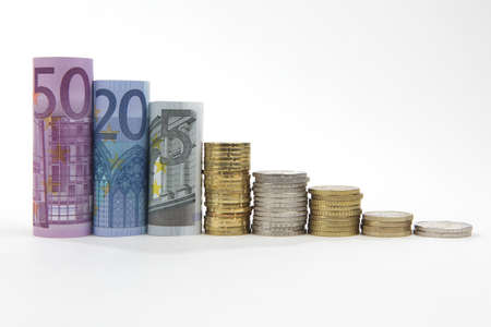 Rolled up Euro bills with coin stacks on white background Stock Photo - 9375179