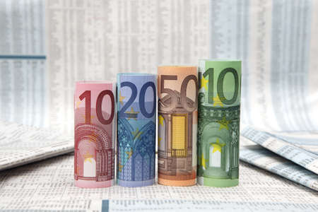 Rolled up Euro bills on financial newspaper Stock Photo - 9375194