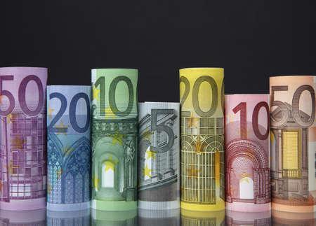 Rolled up Euro bills on dark background photo