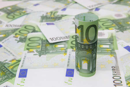 Rolled up 100-Euro bill on Euro background photo