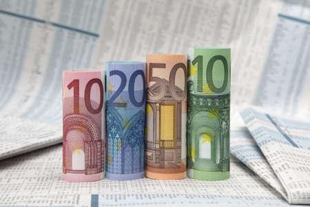 financial newspaper: Rolled up Euro bills on financial newspaper
