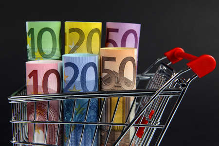 Mini shopping cart with euro banknotes on dark background  photo