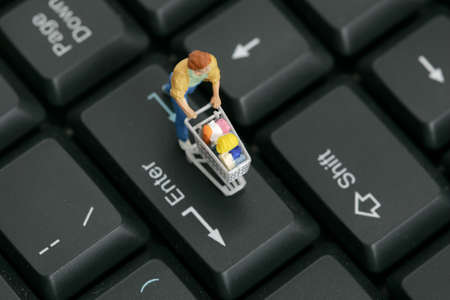 Figurine with miniature shopping cart on a computer keyboard  Imagens