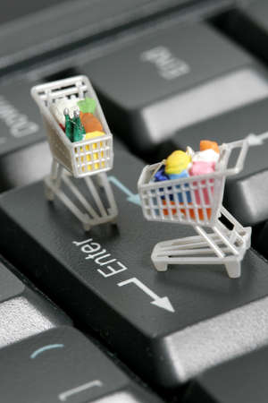 Miniature shopping carts on a computer keyboard  Banque d'images