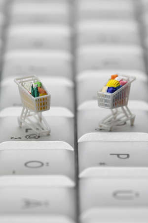 Miniature shopping carts on a computer keyboard. Online shopping concept.  photo