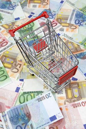 Mini shopping cart standingon euro banknotes Stock Photo - 9539248