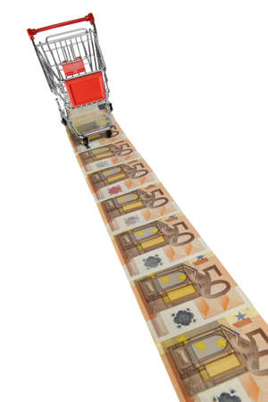 Mini shopping cart standing on a line of euro banknotes on white background photo