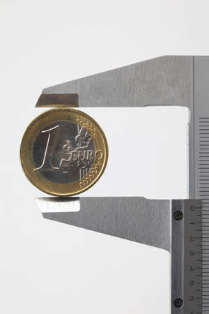 vernier: euro money coin sized by vernier tool on white background