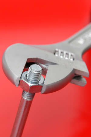 Wrench and bolt on red background  Imagens