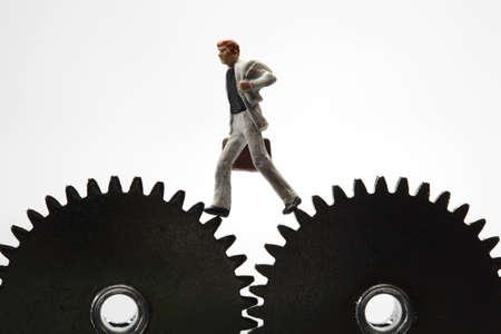 Businessman running on cogwheels - success concept photo