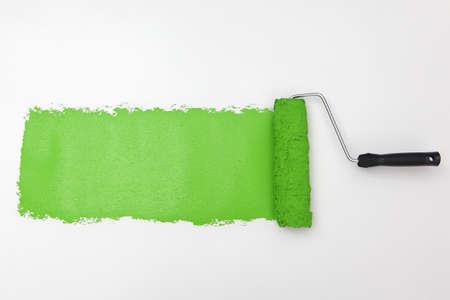roller brush: Green paint roller on white background