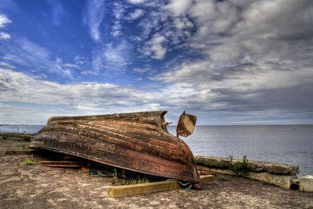 girders: Rusty boat lying on girders on shore with light cloudy ocean background