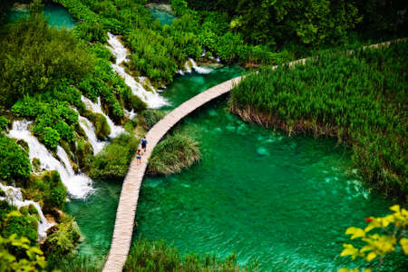 Curving path between riverfalls in green forest, national park Plitvice photo